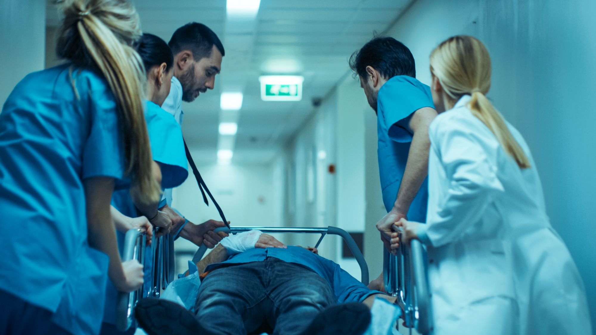 Hospital staff rushing gurney down hallway