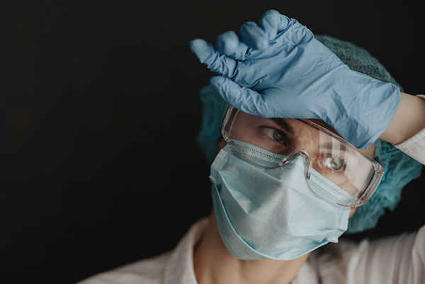 essential worker in protective mask and gloves rests her hand against her forehead