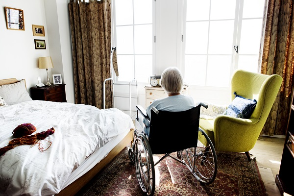 Woman sitting in wheelchair, facing the window